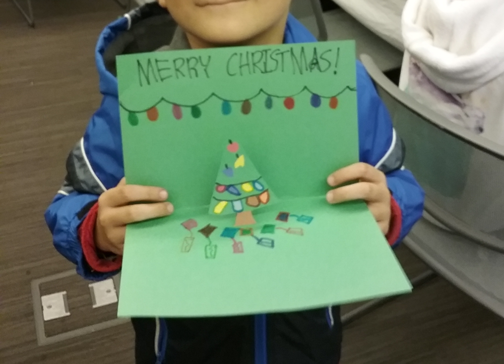 Young visitor displaying his holiday pop-up card.png