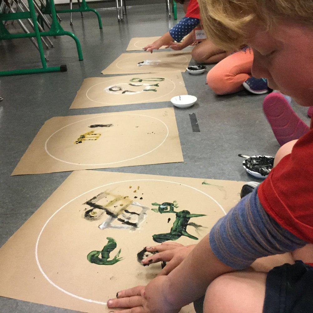 1st graders using their own paint in groundpaintings.JPG