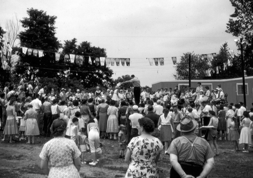After the Fair relocated to the Shippensburg Fairgrounds in 1959, the entertainment stage was the temporary structure shown here with the mobile home in the background serving as the Fair Office.