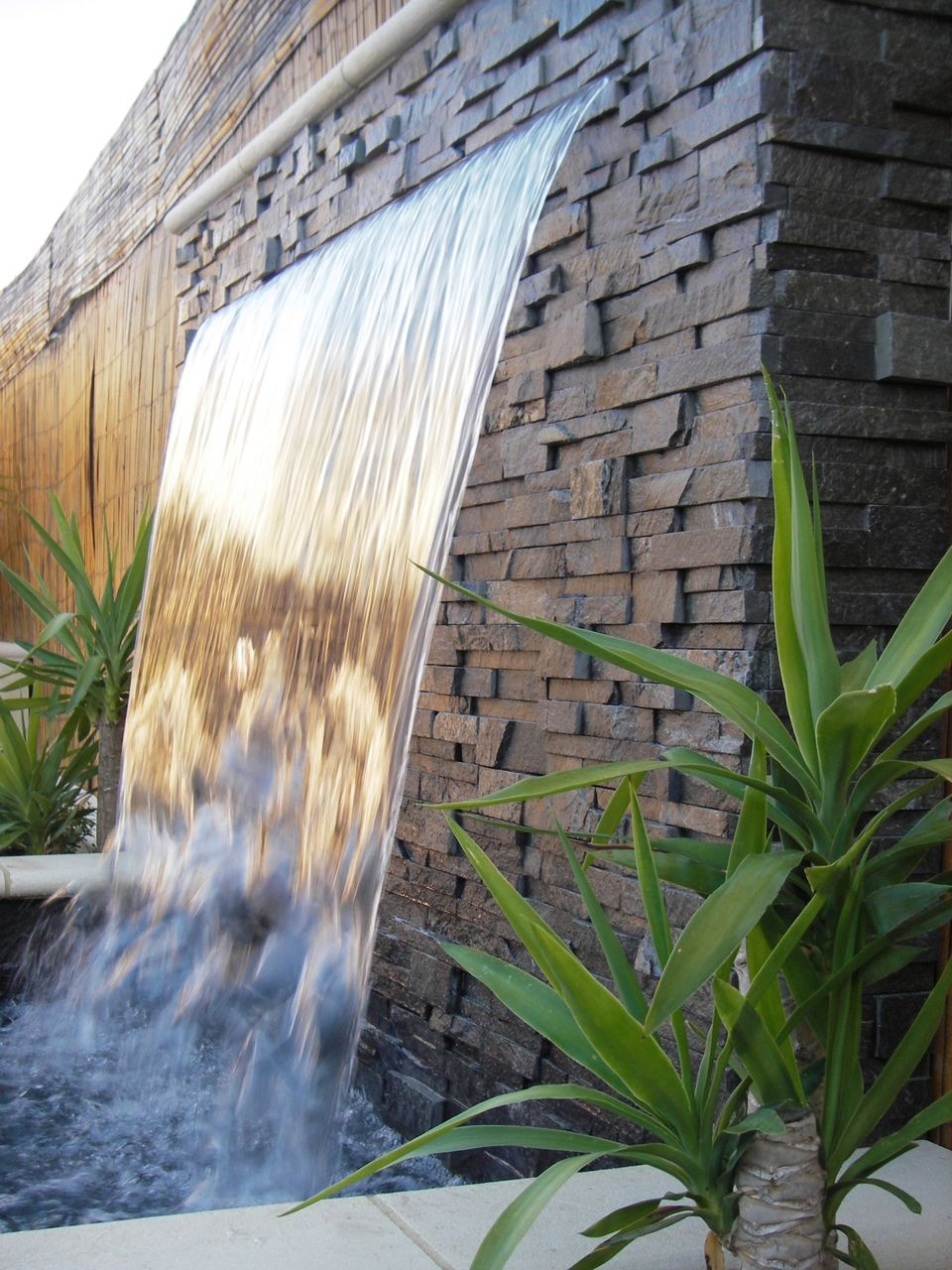 Waterfall features that splash into a reservoir or swimming pool can be built in almost any backyard or landscape.