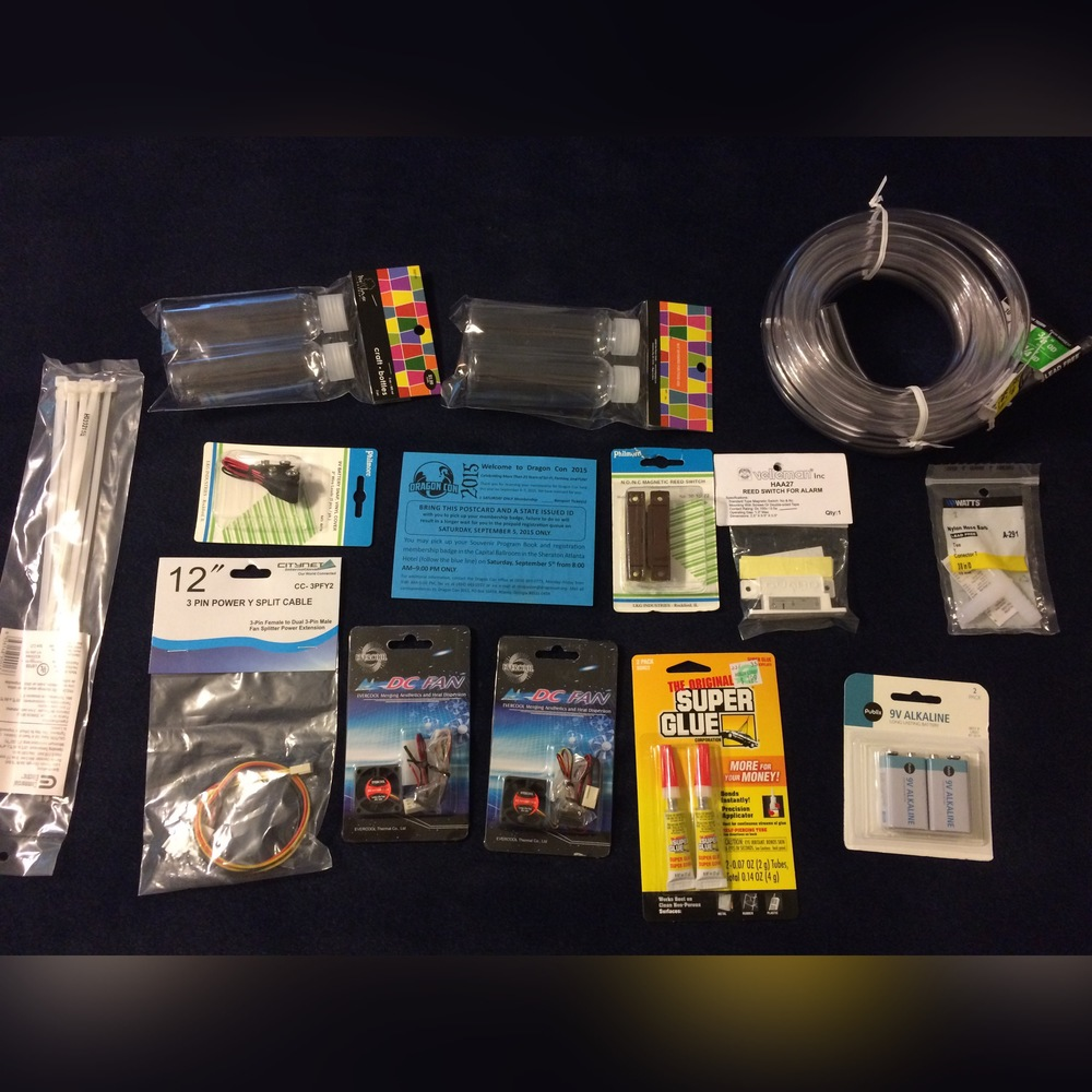 Zip Ties, small plastic bottles, 9 volt battery connectors, Power split cable, 30mm 12v CPU fans, Superglue, Magnetic Reed-switches, t-joint, Vinyl Tubing, 9 Volt Batteries, and of course, the DragonCon ticket card thing!