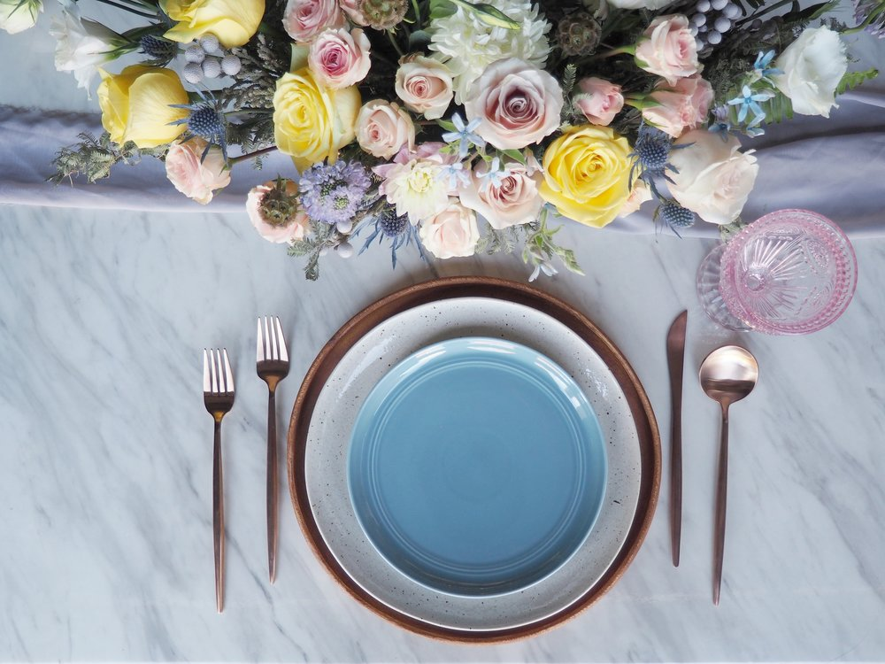 Featuring: Eclectic Pink Goblet, Rose Gold Flatware, Acacia Wood Charger, Speckle Dinner Plate & Blue Salad Plate