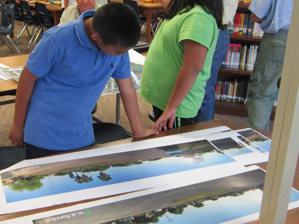 A student pours over panoramas during a community meeting