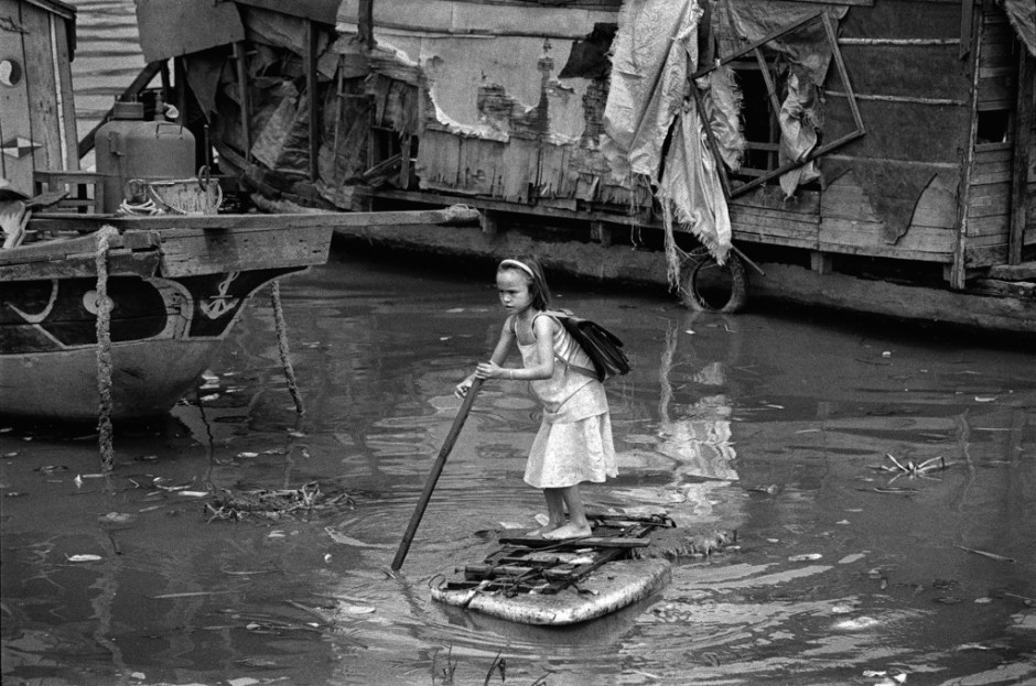 This girl lives with her family on their boat moored on the Saigon River. To get to school, she punts herself to the bank standing on a piece of Styrofoam packing material..jpg