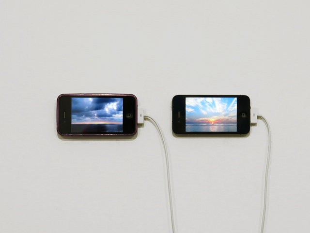 "David Horvitz 'The Distance of a Day', 2013    Two videos, 12 minutes each. Installation view, Chert, Statements, Art Basel, 2013   In early February I asked my mom to go and watch the sunset and make a video. She did this from the Palos Verdes Peninsula, where I used to watch the sunset when I lived in California. She made the video with her iPhone taped to a metal barrier that protects people from falling over the cliffs.  In synchronicity with her, I too was looking at the sun and making a video. From my perspective the sun was rising. I had calculated where the the sun would be seen as rising at the exact same moment it was seen as setting in Los Angeles. In early February this was the Maldives, a location which may not exist in the near future due to the rising of the seas.  As my mom watched the sun set into the Pacific Ocean, I was watching it rise over the Laccadive Sea. Synoptic is a useful term here. It comes from the Greek syn, meaning ""together"", and optic, meaning ""seen"". Though separated by thousands of miles, we were watching the sun together.  The title, The Distance of a Day, is a reference to the idea of the journey. Originally, journey meant the distance one traveled in a day. Here, the spatial distance that separated my mother and myself was not defined by the distance one could travel in a day, but by the day itself. By the delimitations of a day - where the sun rises and where the sun sets.  Phones were chosen to make (and display) the video because they are devices that orient us spatially and temporally. They are like contemporary pocket-watches and compasses that we carry with us. They coordinate and synchronize us. They broadcast moments instantaneously across distances. Or, what seems to be instantaneously. There is always some delay.  The same two phones that were used to shoot the videos, that were once on opposite sides of the world, are now used to display the videos. They are now only inches away.  Right now somewhere the sun is simultaneously setting and rising. Someone or something is probably bearing witness to this."