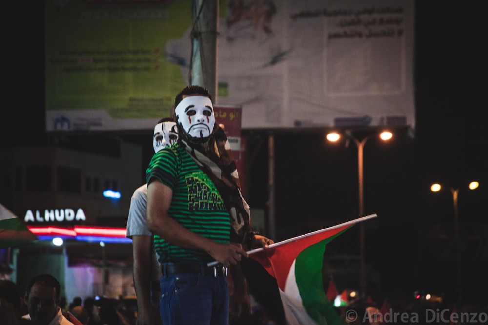 Two protestors survey the crowd in the growingly popular 'V for Vendetta' mask. Concealing your identity can be crucial at these sort of demonstrations for Palestinians participating in protests fear that the Israeli military will use photos from demonstrations like these to accuse them of breaking laws.