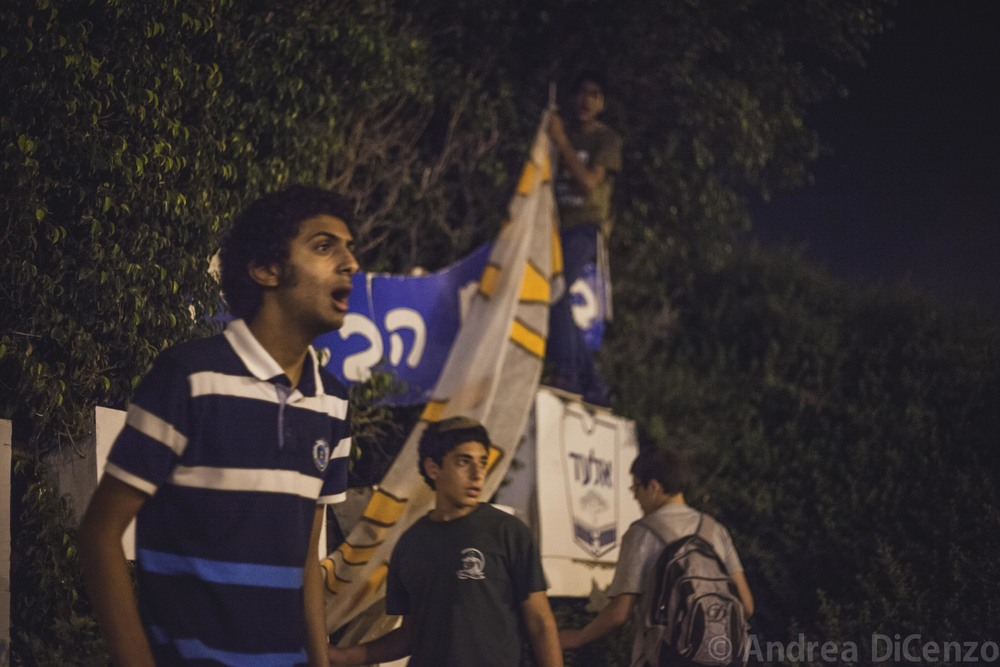 A group of boys from the Israeli settlement of El Ad cautiously addresses strangers passing by as they try to erect a large homemade banner on the evening the bodies of the three missing Israeli teenagers were discovered.