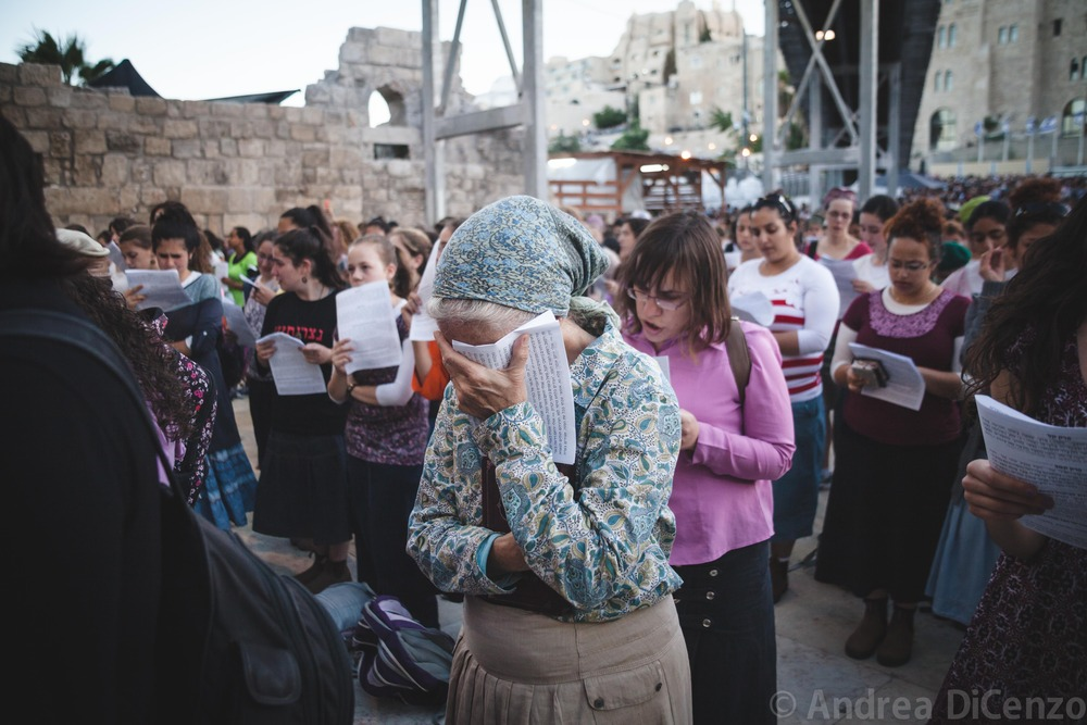 A Jewish woman puts her head in her hand in distress at a prayer vigil that is held for the missing teenage Israeli boys. The teenagers had been missing for four nights.
