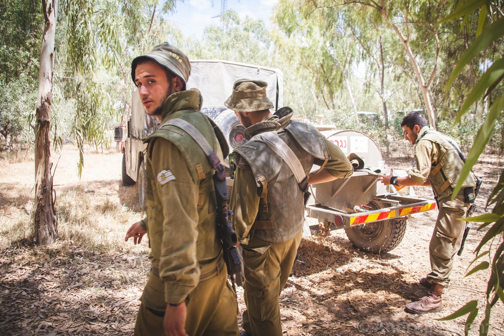 Motor rockets can be heard going off as close as 500 meters away as the soldiers gather to receive further command as the ground incursion begins as part of Operation Protective Edge.