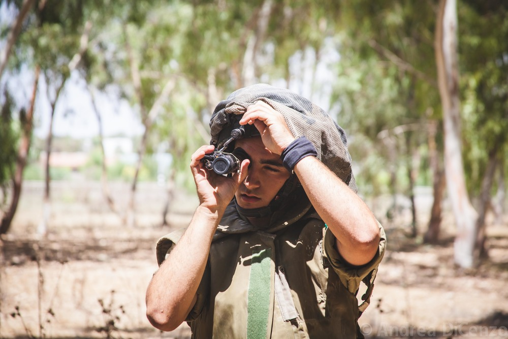 A solider checks his night vision device while awaiting instructions on the north eastern border of Gaza and Israel. 18,000 soldiers were called up to the border of Gaza in addition to the 40,000 that area already in position.