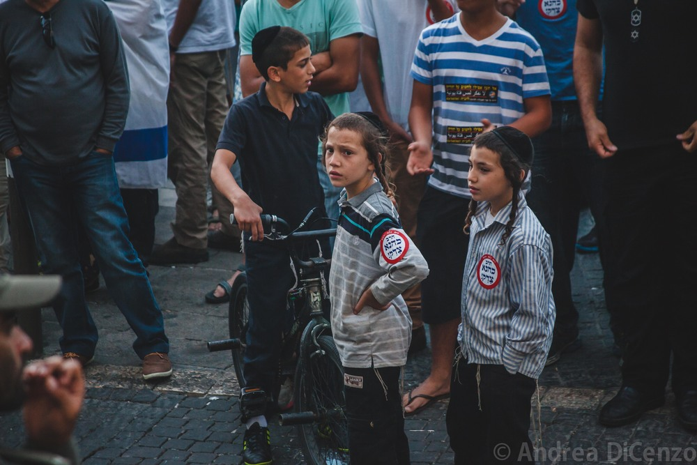 Young children with right wing stickers displayed look on as the protestors continue to fight with one another.