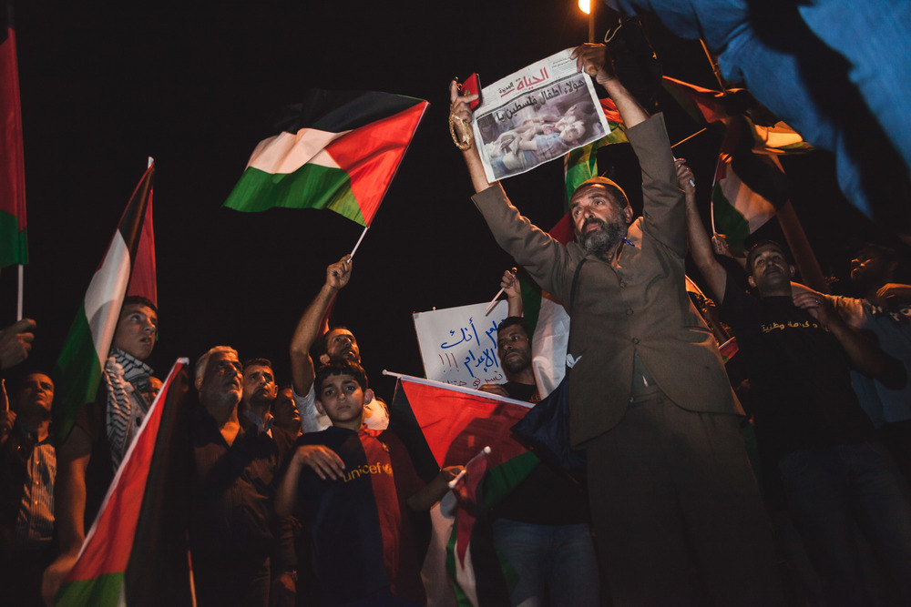 While the evenings protest was still in its early stages, a demonstrator holds up a newspaper with an image from Gaza prominently displayed as thousands gathers around the main junction of Al-Amari Refugee Camp waiting for the demonstrations to begin.