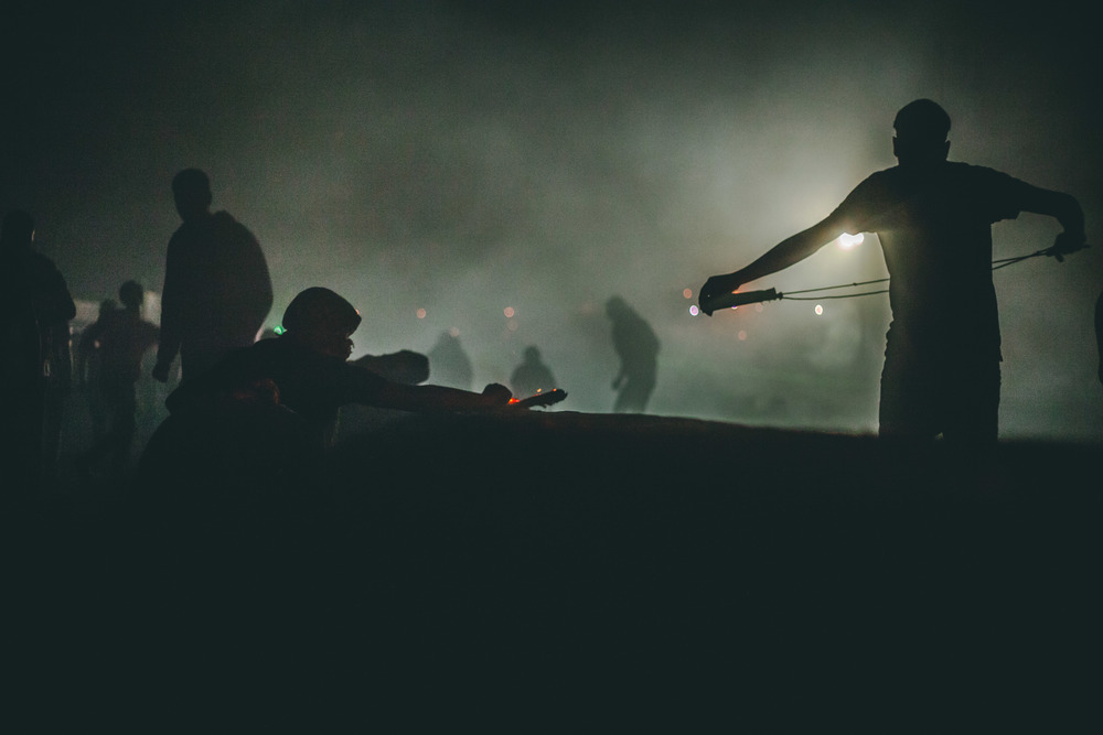A Palestinian protestor preps his sling shot in a silhouette of tear-gas and smoke.