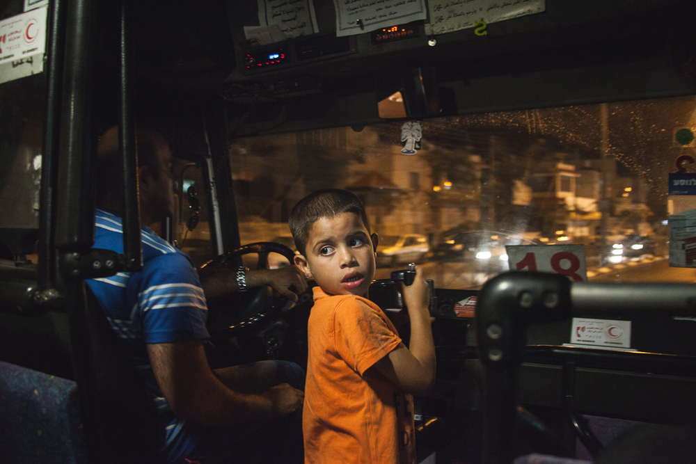 A little boy looks back at commuters on a packed bus in Ramallah as the radio reports the discovery of the three missing Israeli teen's bodies in the West Bank.