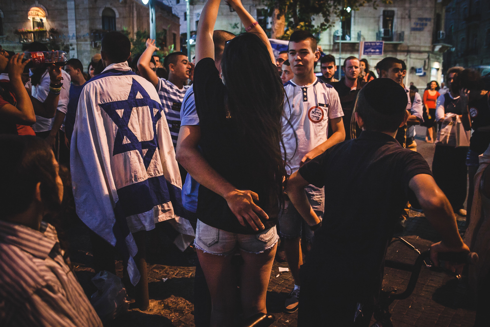 A couple embrace during a extreme right protest in Jerusalem. The protest didn't have a license and the police were present to make sure the demonstration was contained.