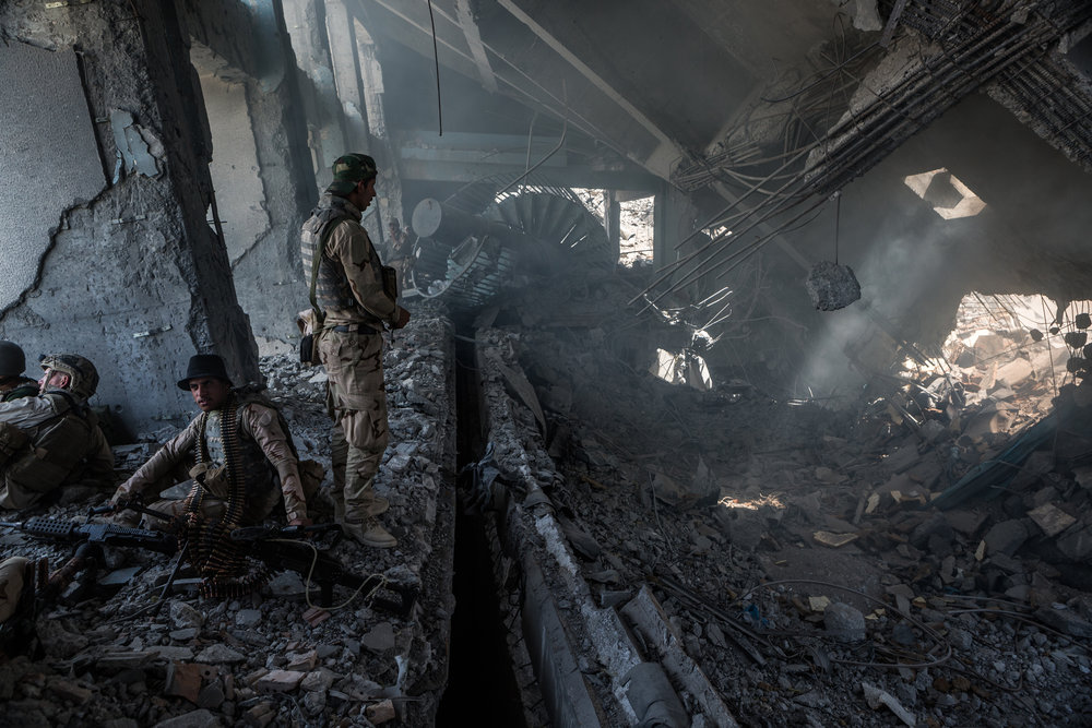 Members of the Iraqi army fortify a new position inside the remains of the Old Mosul Hotel in al-Shifa neighborhood during a newly launched assault to reclaim the last remaining districts of western Mosul from the Islamic State.