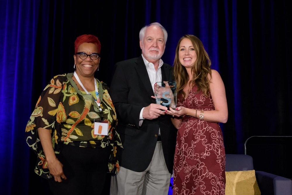 Danae Davis (l) from Milwaukee Succeeds Initiative and the Strive Together Board, celebrates the presentation of the Bill Henningsgaard Cradle to Career Champion Award to Dr. John Stockwell of the Spartanburg Academic Movement. The award was presented by StriveTogether network navigator Bridget Jancarz (r) in Phoenix, Arizona.