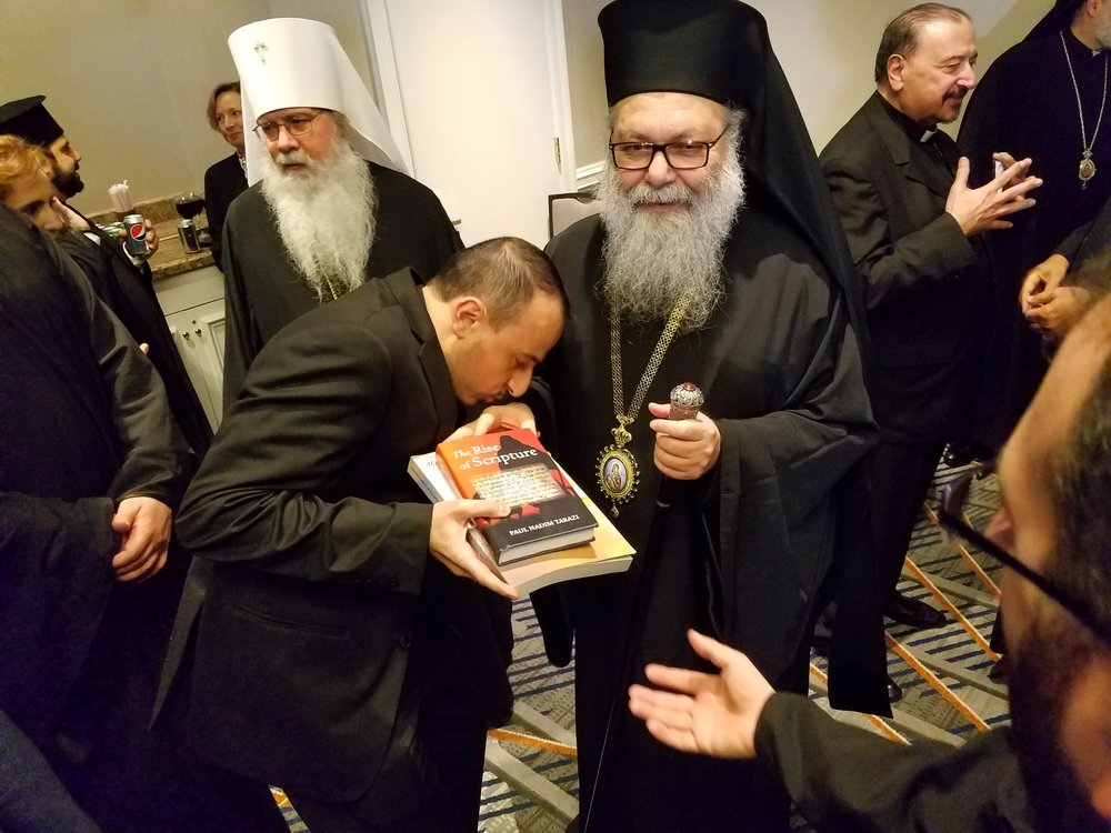 The Very Rev. Fouad Saba, pastor of St. George in Coral Gables, FL, presents a copy of the book to Patriarch JOHN X.