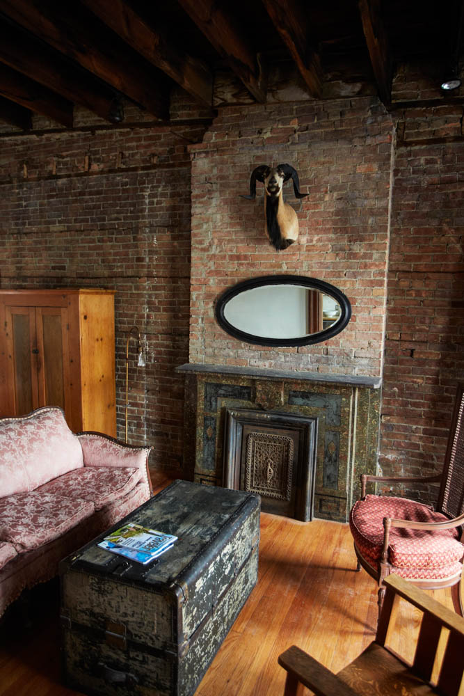Taxidermy and an antique mirror on display over the fireplace in the Bowler.