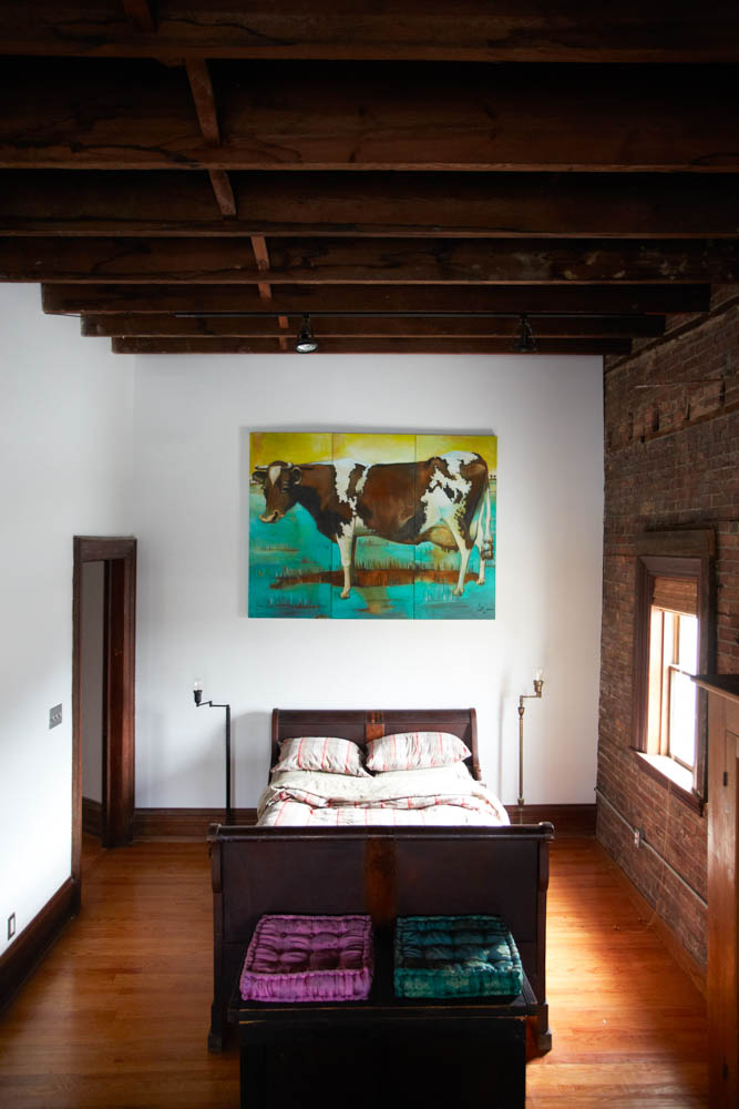 Original americana artwork hangs over the vintage sleigh bed in the Bowler suite.