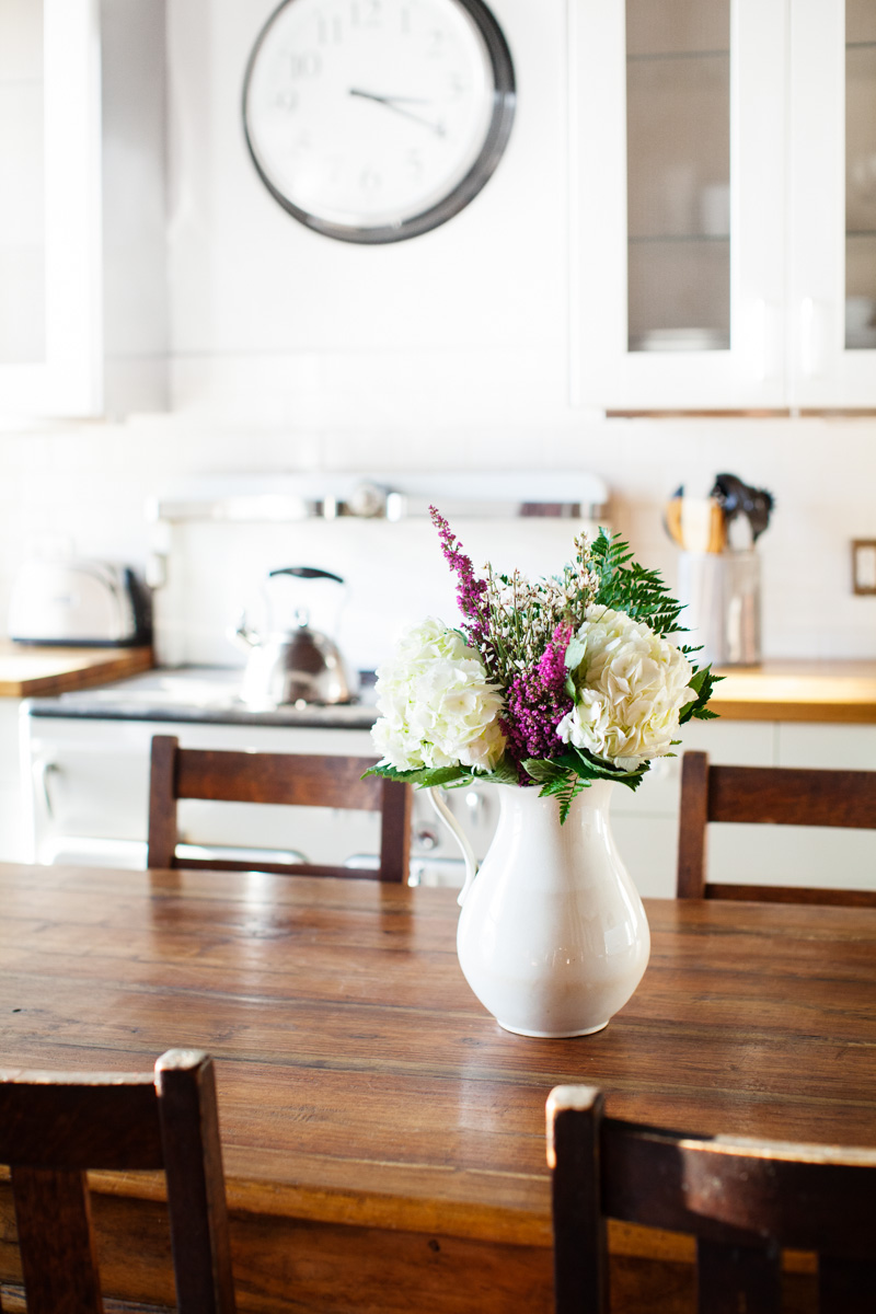 Fresh cut flowers sit in a white pitcher on the dining table.