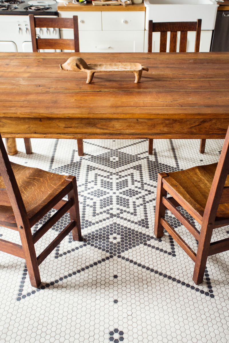 A vintage farm-style dining table sits on originally-designed octagon tile floors.