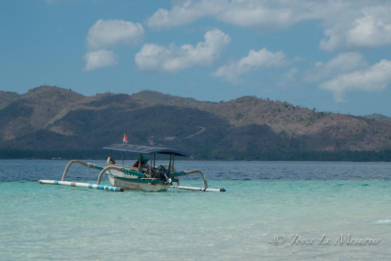 an outrigger canoe in the turquose waters of the Gilis
