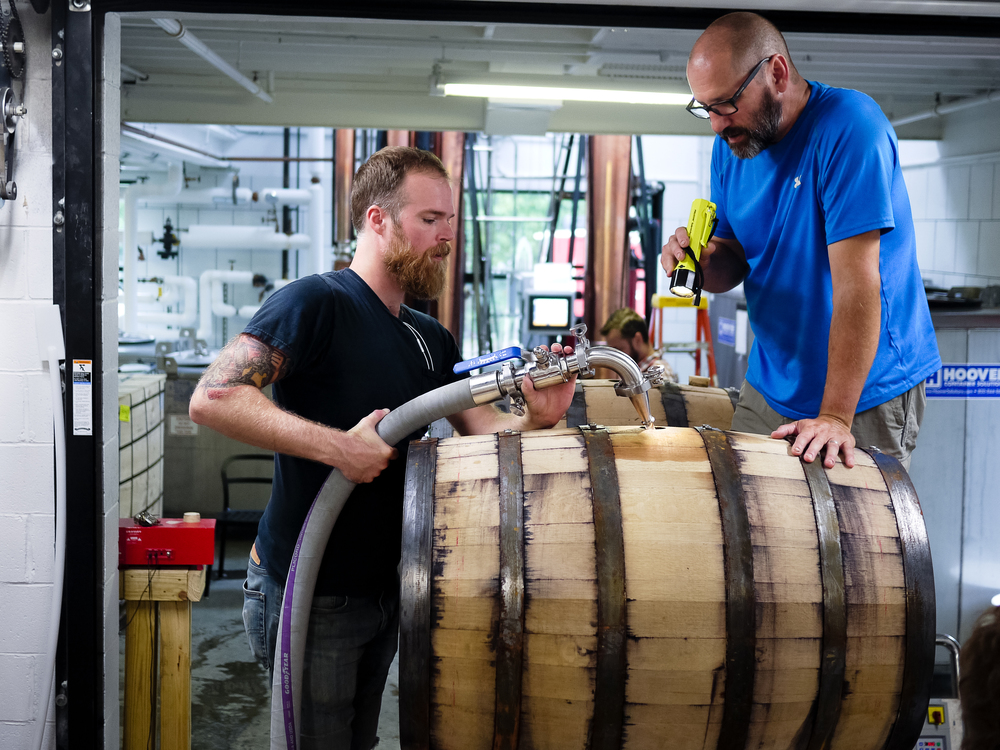 Jason and Doug filling whiskey barrels at the distillery.