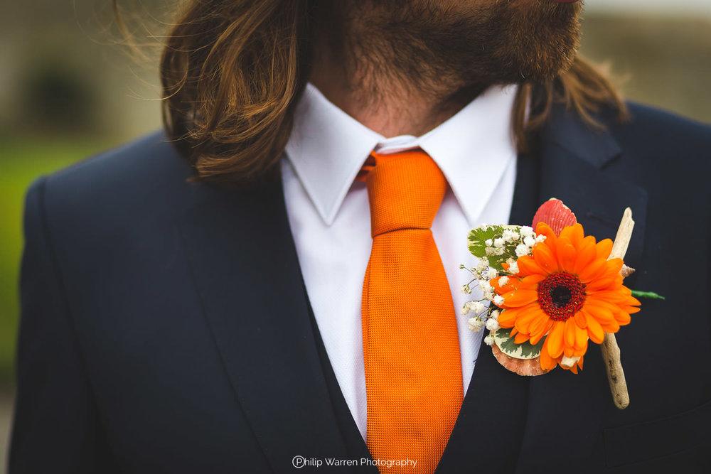 grooms suit with bright orange tie