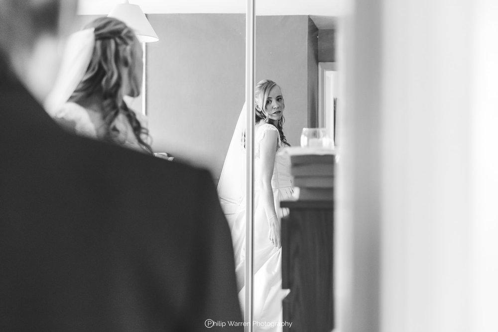 bride in her wedding dress looking in the mirror