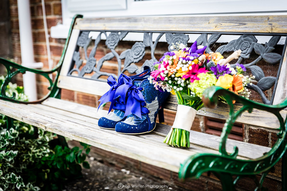wedding shoes and bouquet of flowers on a bench