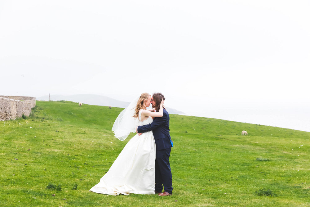 bride and groom on the cliffs by southerndown