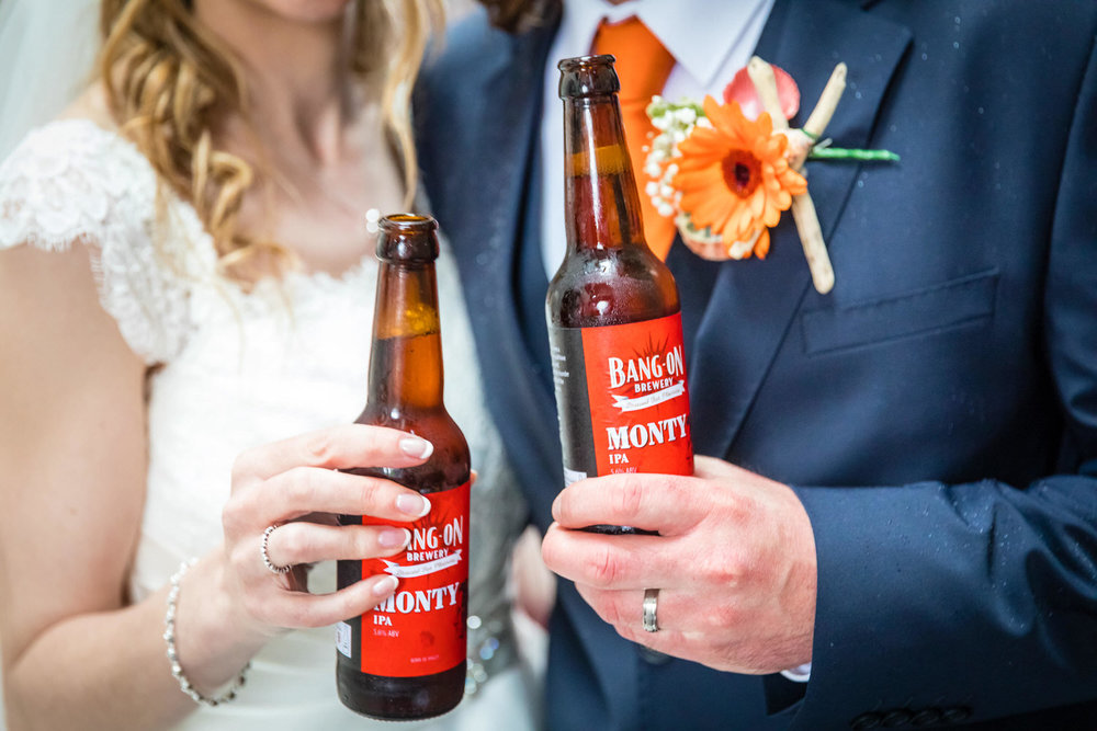 bride and groom toasting beers during wedding