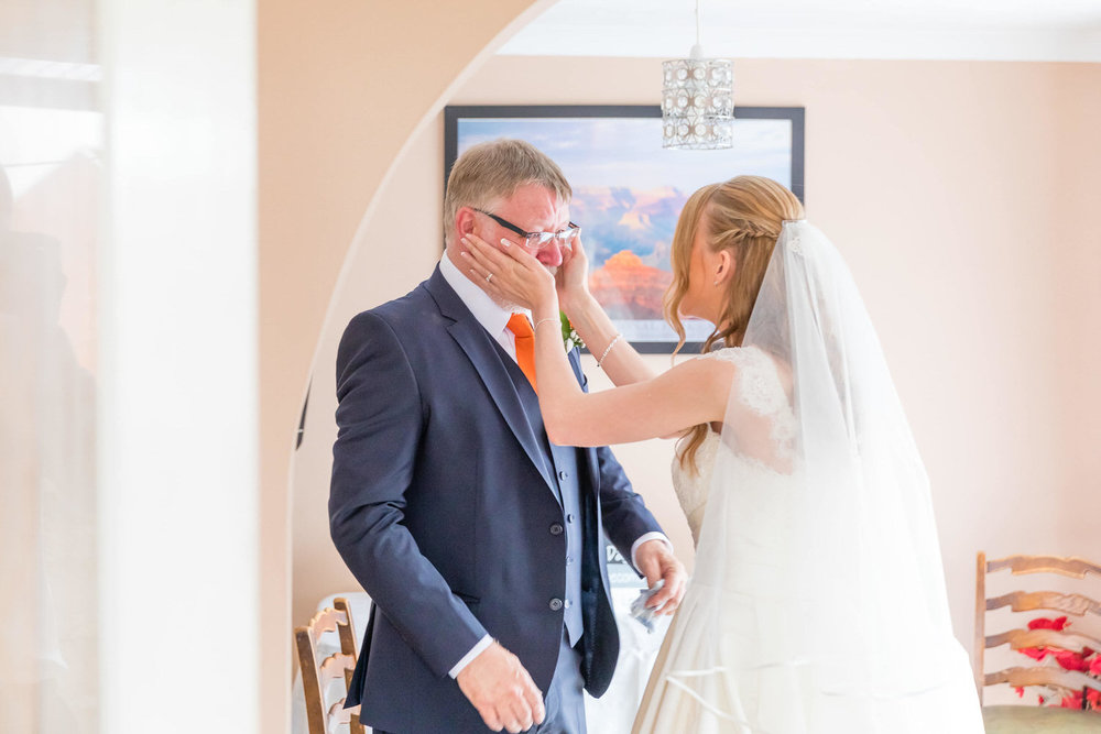 bride comforting her dad before wedding