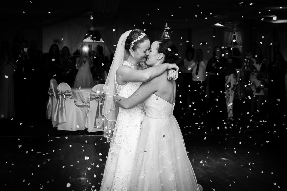 two brides share a kiss during their first dance after the weddi