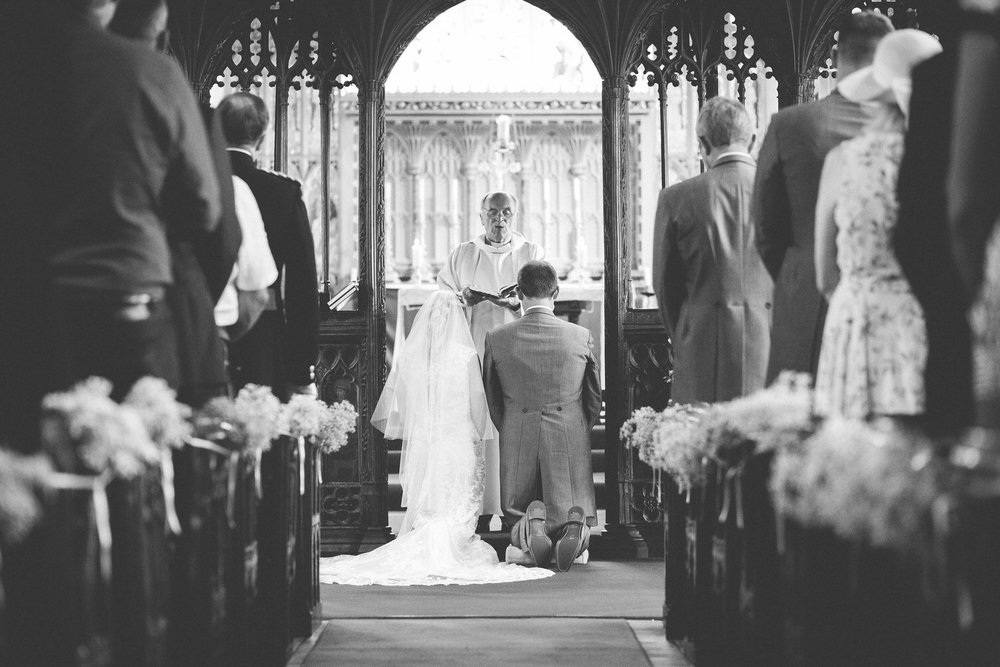 bride and groom kneeling during church ceremony