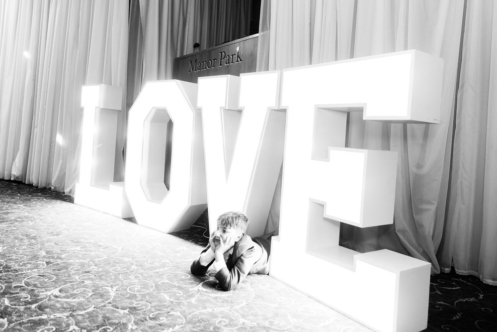 boy sitting underneath light up love letters