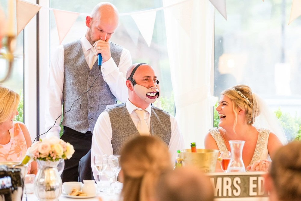bride laughing at the groom during best man speech