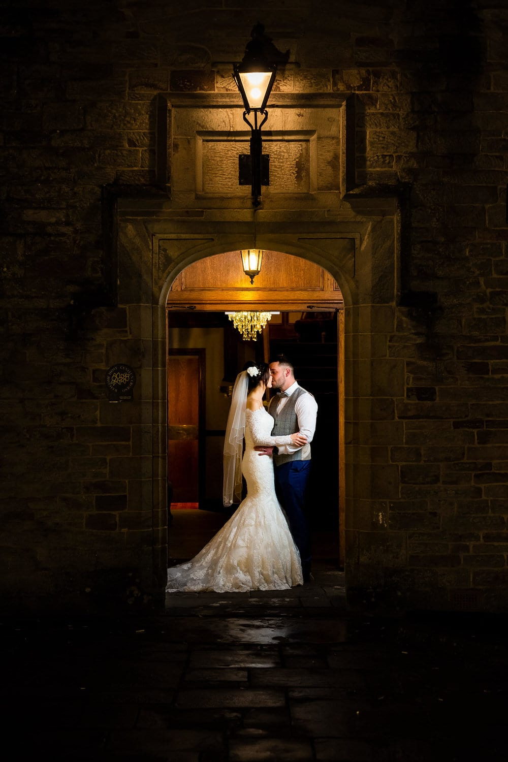 bride and groom kissing in doorway of bryngarw house