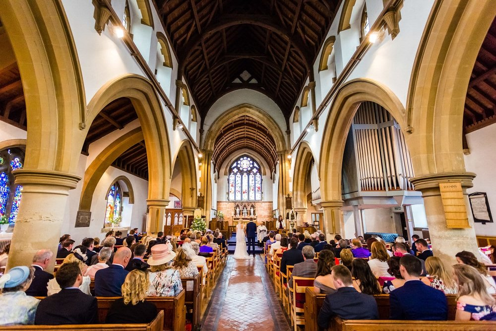looking down the aisle in church at the bride and groom
