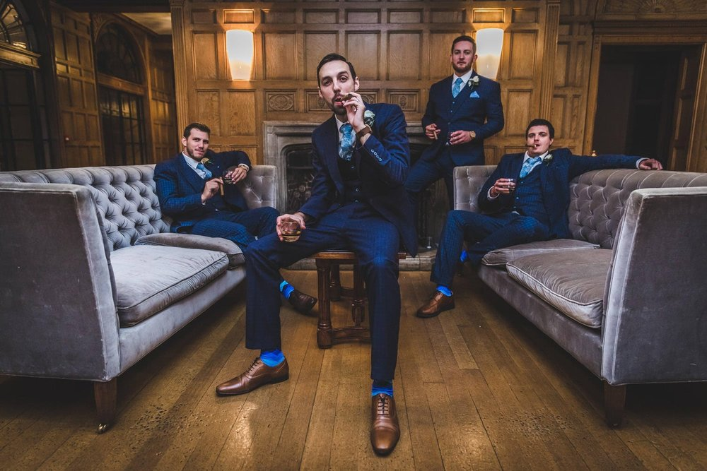 groom and best men sat in the chairs at coomble lodge wedding