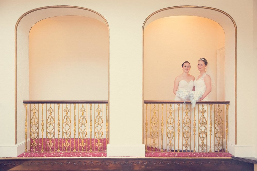 two brides standing on the blancony at manor parc swansea