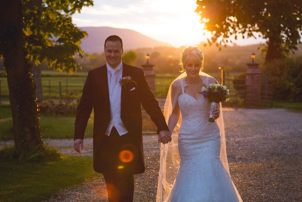 bride and groom walking towards the camera with the sun behind