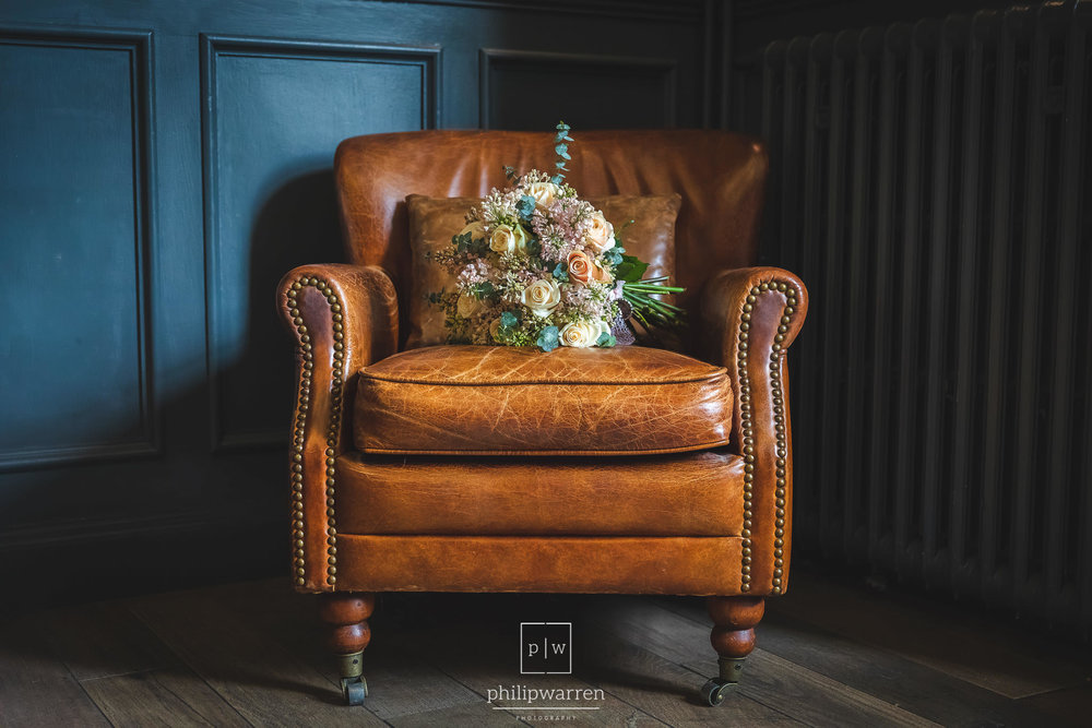wedding boquet sat on a leather chair in Bryngarw House Hotel