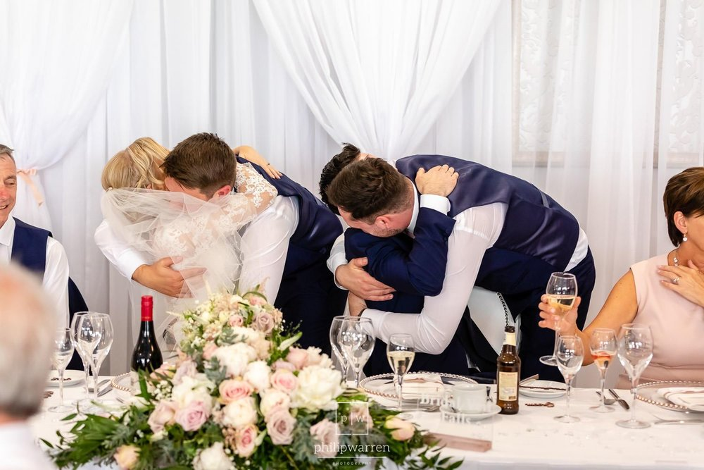 best men hugging bride and grooms during speeches