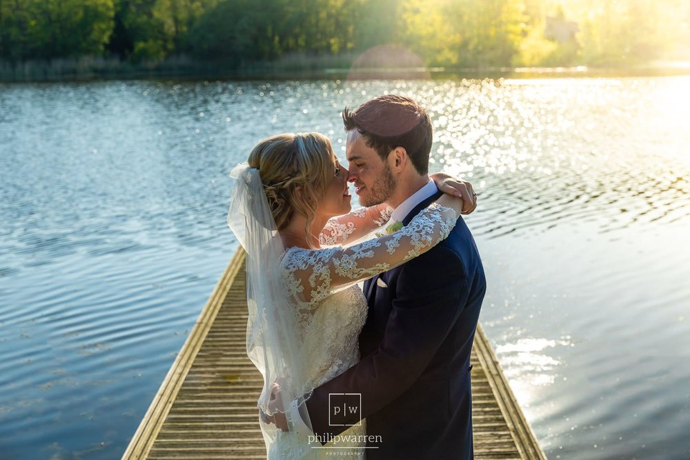 bride and groom kissing at sunset on the jetty at hensol