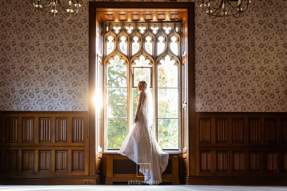 bride standing in the window of ceremony room in hensol castle