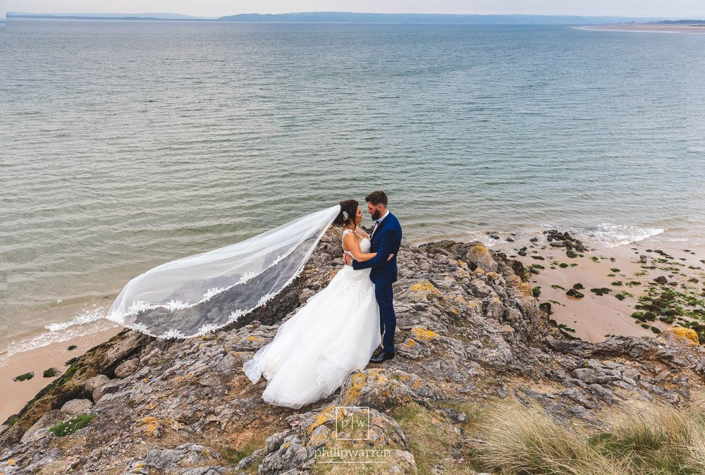 bride and groom on the rocks at gower peninsula