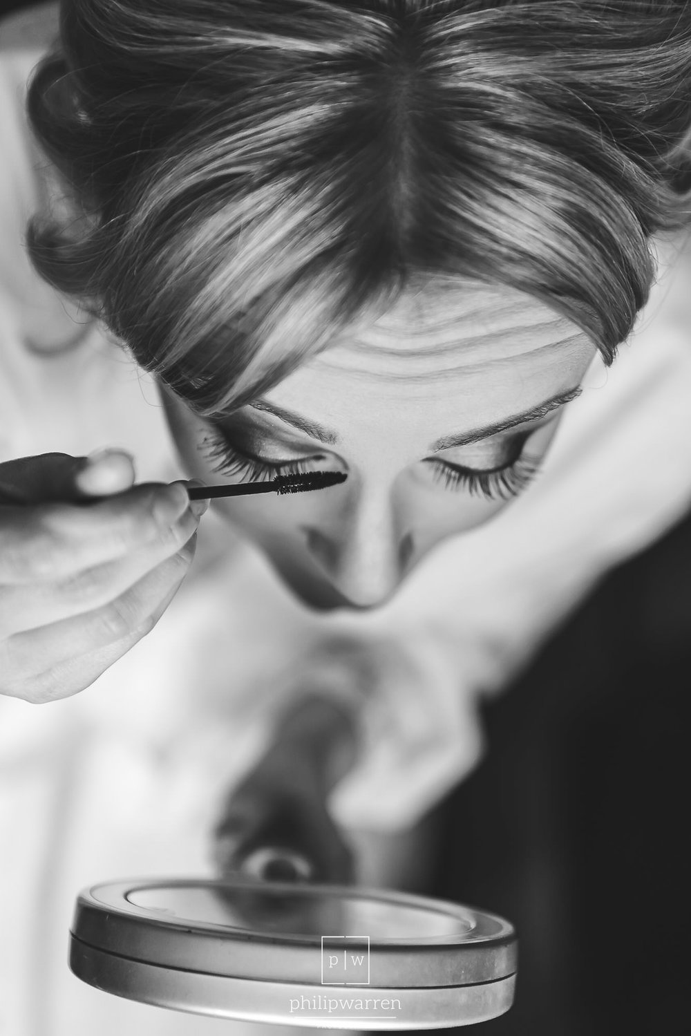 bride doing makeup in mirror taken from above