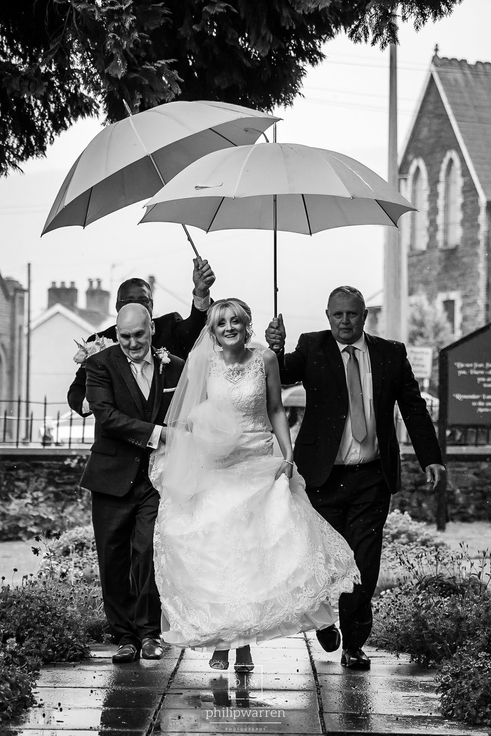 bride walking up to the church in the rain with umbrellas